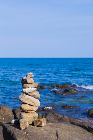 stack stone: Natural stack stone with natural blue ocean skyline background Stock Photo