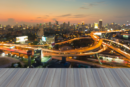 interchanged: Opening wooden floor, Aerial view burred light city interchanged road and office building background during sunset Stock Photo