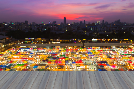 Opening wooden floor, Blur bokeh of Flea market aerial view with beautiful sky after sunset Stock Photo