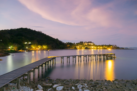 leading the way: Wooden walk way leading to the seacoast night view with mountain background Stock Photo