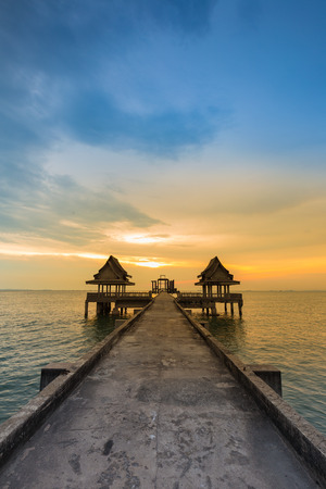 leading the way: Walking way leading to lonely temple in ocean with beautiful natural sunset sky background Stock Photo