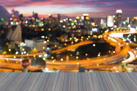 Apertura de piso de madera, luces bokeh borrosa ciudad intercambiada y vista de fondo de ciudad centro de la ciudad