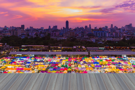 Opening wooden floor, Colorful night market in Thailand with city downtown background