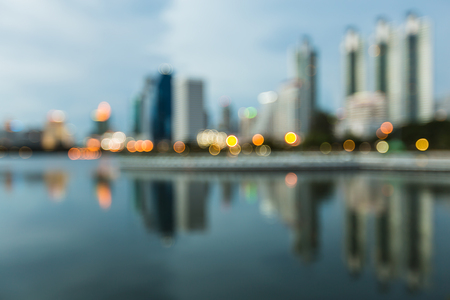 Blurred bokeh city with water reflection at twilight Stock Photo