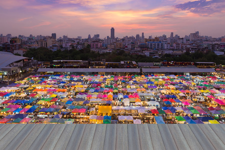 Opening wooden floor, top view night weekend market with city downtown and dramatic sky background