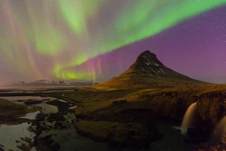 De nachtmening van noordelijk lichten over vulkaan Kirkjufell met volledig van ster op de hemel, natuurlijke het landschapsachtergrond van IJsland Stockfoto