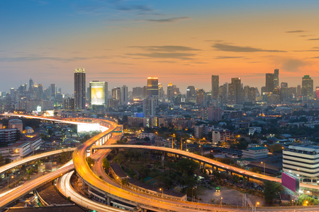 Sunset sky over highway interchanged with city central business background, Bangkok Thailand