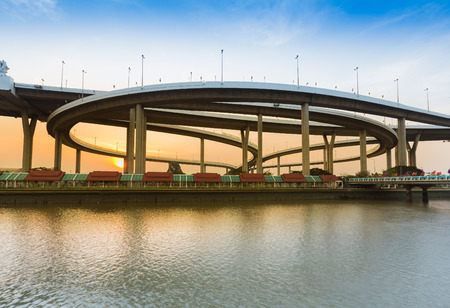 Sunset behind highway interchanged with river front, with clear blue sky background Stock Photo