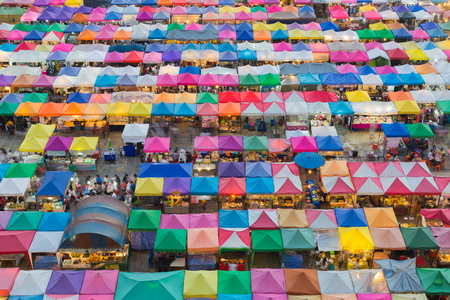 Multiple colours weekend market top view, city downtown background Stock Photo