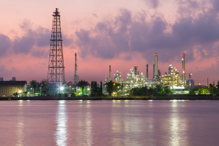 Oil refinery river front night view, industrial background Stock Photo