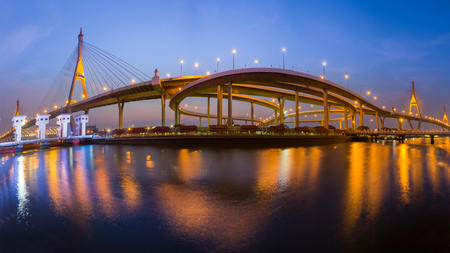 Panorama Twin suspension bridge connect to highway interchanged river front, night view Stock Photo