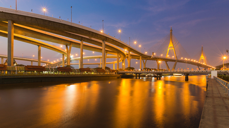 Night view over Suspension bridge connect to highway interchanged river front, Bangkok Thailand landmark Stock Photo