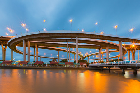Round highway interchanged with blue twilight sky background river front, Bangkok Thailand Stock Photo