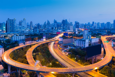 Long exposure, highway road curved with city downtown background at twilight