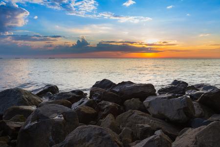 Rock over the beach skyline with sunset sky background