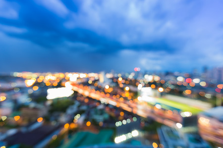 Blurred lights aerial view city and road curved twilight sky background
