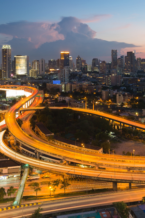 interchanged: Long exposure highway interchanged with city downtown background at twilight
