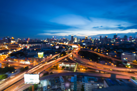 interchanged: Blurred light highway interchanged with city downtown twilight skyline background
