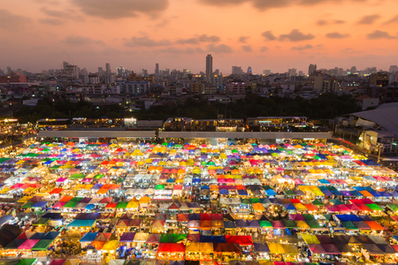 Aerila view, multiple colours night market top view with downtown background during sunset Stock Photo