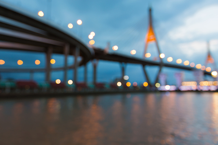bridged: Blurred bokeh lights suspension bridged over city river, abstract background