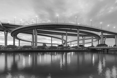 Blanco y negro, intersesction redondo de la carretera con vista nocturna de reflexión
