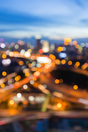 Twilight blurred bokeh lights city road interchanged with blue sky background