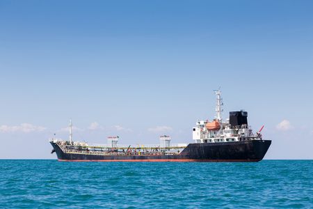 Oil cargo ship in ocean skyline with clear blue sky background