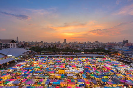 Aerial view over multiple colour weekend market roof top with beautiful sunset sky background