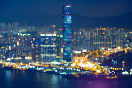 Nights blurred bokeh light Hong Kong city business downtown over Victoria Bay
