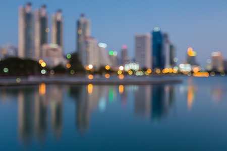 Twilight blurred bokeh office building with reflection in public park, abstract background Stock Photo