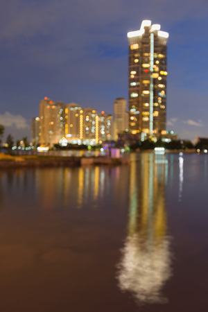 Defocused city building river front with reflection night view, abstract background