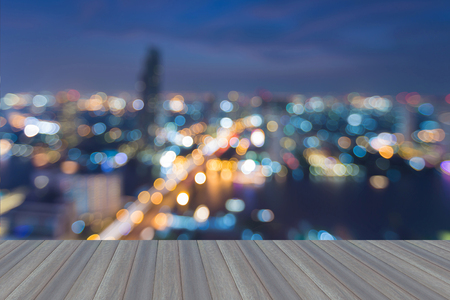 Opening wooden floor, city business downtown blurred light skyline night view, abstract background