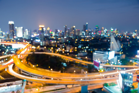 Aerial view city downtown and interchanged overpass blurred bokeh light night view, abstract background