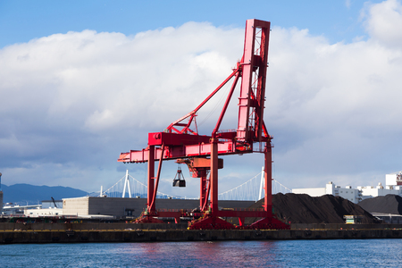 Red transportation crane over sea port with blue sky background