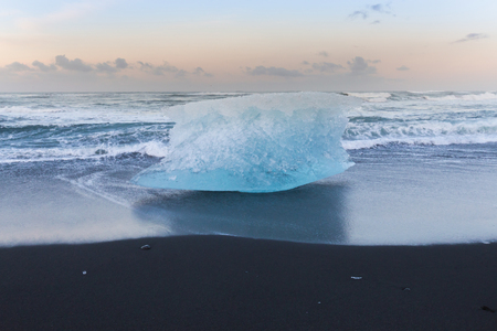 icefjord: Ice breaking on black sand beach ocean skyline background, Iceland winter landscape background
