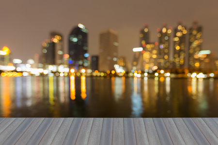 keyword: Opening wooden floor, Night blurred bokeh light office building with water reflection, abstract background