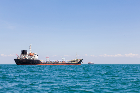 unloading: Oil transportation ship with ocean and clear blue sky background Stock Photo