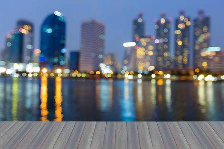 Opening wooden floor, Twilight blurred bokeh office building with water reflection, abstact background