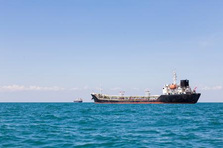 unloading: Oil logistic transportation ship over ocean skyline background