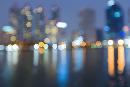 Blue twilight city office building with reflection blurred bokeh light, abstract background