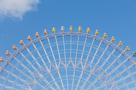 Half of big giant ferris wheel against blue sky background Stock Photo