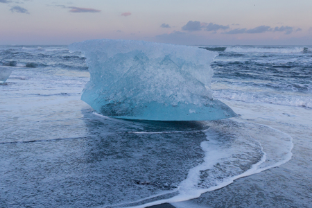 icefjord: Ice breaking over black sand beach skyline, Iceland Jakulsarlon natural landscape background Stock Photo