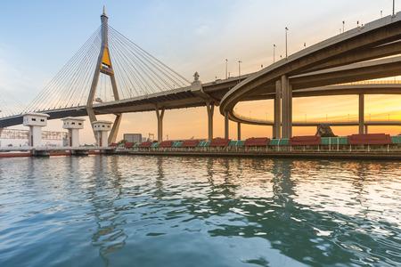 Sunset over suspension bridge connect highway river front, Bangkok Thailand