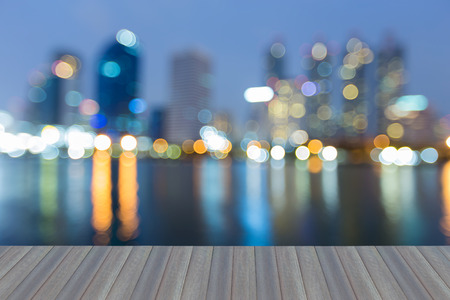 Opening wooden floor, Night blurred bokeh blue twilight office building and reflection, abstract background
