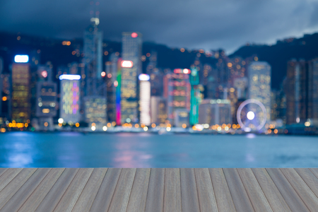gloom: Opening wooden floor, Blurred bokeh light night view Hong Kong business downtown, abstract background Stock Photo