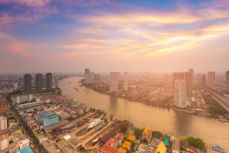 Sunset sky background over river curved and city aerial view, Bangkok cityscape downtown Thailand