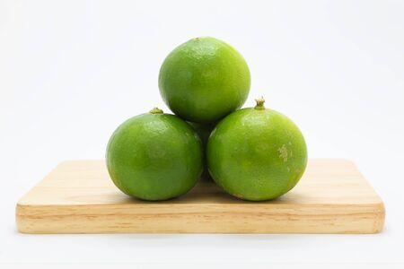 Fresh limes on wooden board, on white background