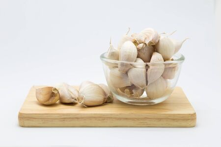 Fresh rood garlic on wooden board, on glass cup, on white background Stock Photo