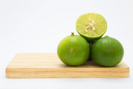 Fresh slice limes on wooden board, on white background