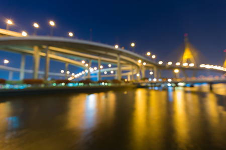 Night blurred bokeh light bridge and highway river front reflection, abstact background